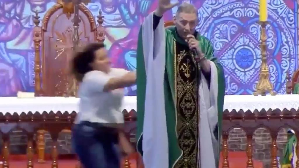 Mujer empuja y tira del escenario a sacerdote en plena misa.